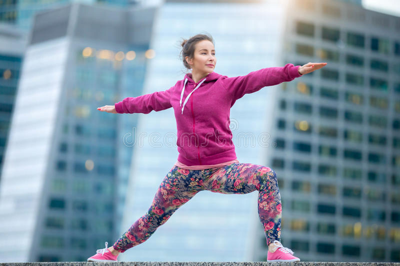 Woman wearing pink in Warrior 2 pose stock image