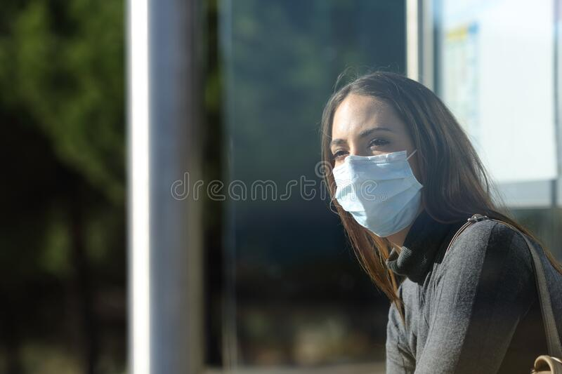 Woman wearing a mask waiting in a bus stop royalty free stock photo