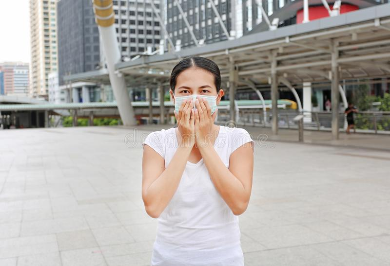 Woman wearing protective mask to protect pollution and the flu. Standing at public area royalty free stock image