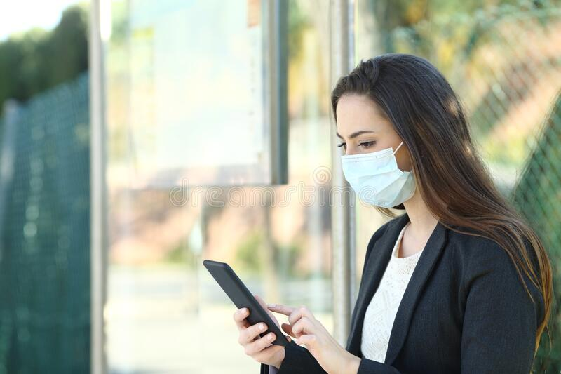 Woman wearing a protective mask using phone royalty free stock photo