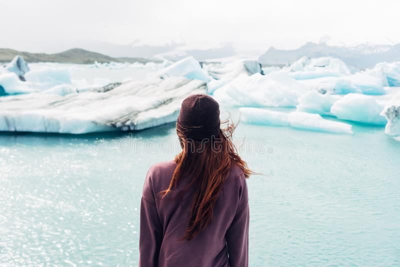 Woman Wearing Purple Shirt Overlooking at Body of Water and Snow Covered Field stock photo