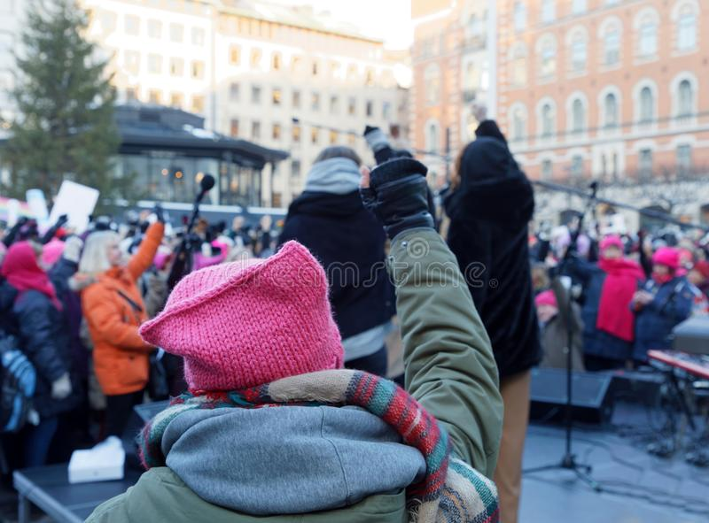Woman wearing Pussyhat raising her fist in the Womens March, a w royalty free stock images