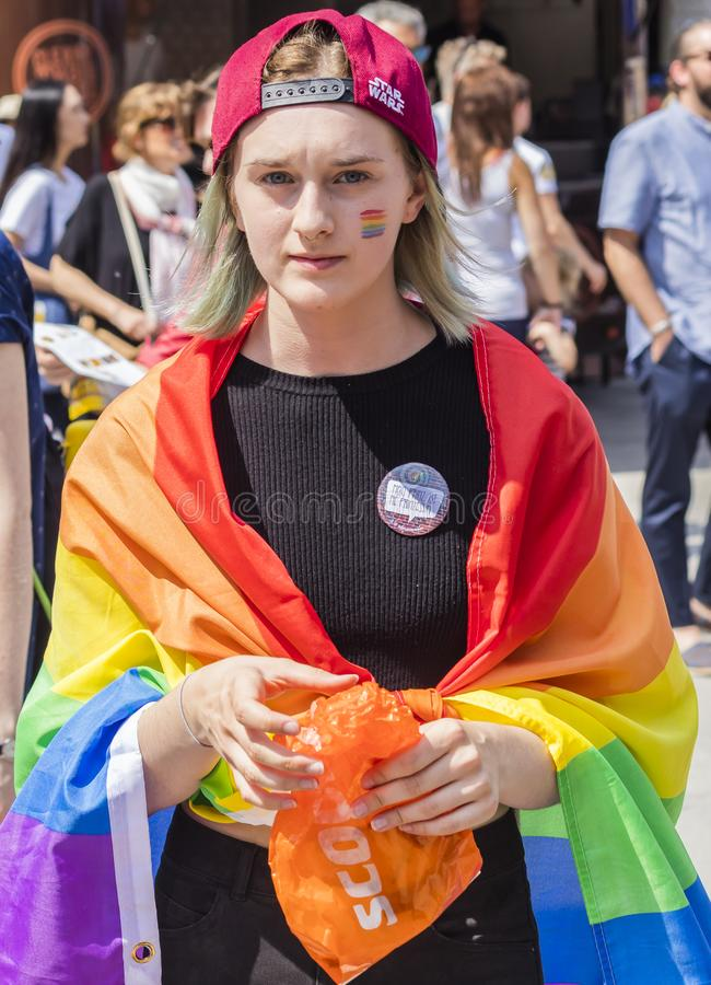 2018: A woman wearing a rainbow flag attending the Gay Pride parade also known as Christopher Street Day CSD in Munich, Germany.  stock photos
