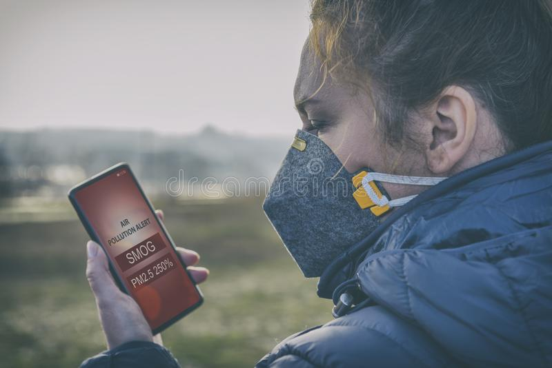 Woman wearing a real anti-smog face mask and checking current air pollution with smart phone app. Woman wearing a real anti-pollution, anti-smog and viruses face royalty free stock photo