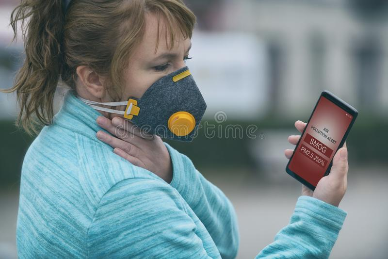 Woman wearing a real anti-smog face mask and checking current air pollution with smart phone app stock image