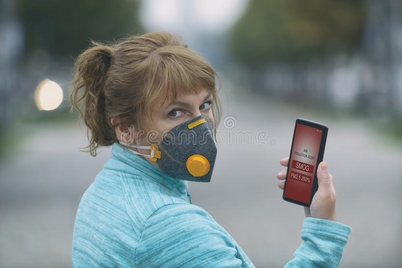 Woman wearing a real anti-smog face mask and checking current air pollution with smart phone app stock photography