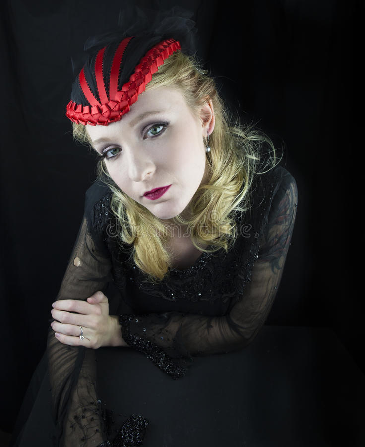 Woman wearing red and black hat. Young woman wearing red and black hat in black dress stock images