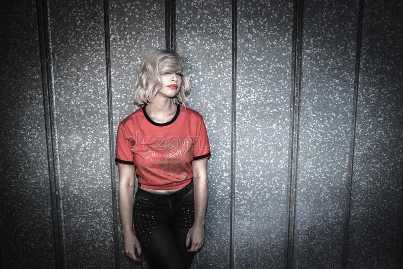 Woman Wearing Red and Black Scoop-neck Shirt and Black Bottoms Leaning on Gray Wall royalty free stock photo