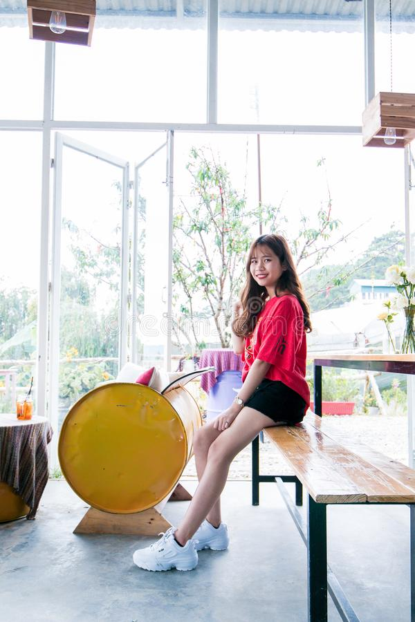 Woman Wearing Red Blouse and Black Short While Sitting on Table stock photo