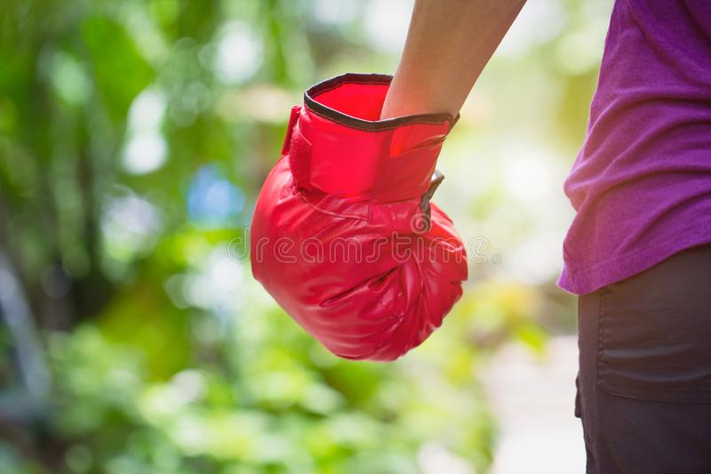 Woman wearing red boxer grove standing against green nature bokeh outdoor back view with copy space. business fighting victory stock image