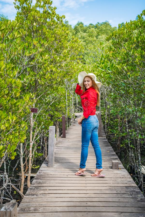 Woman wearing red clothes in wooden bridge at Tung Prong Thong or Golden Mangrove Field, Rayong, Thailand. Woman wearing red clothes in wooden bridge at Tung stock image