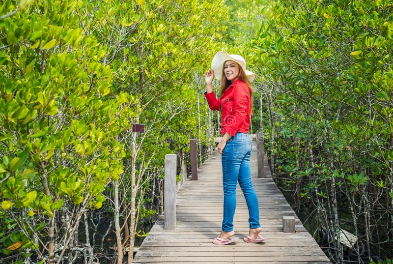 Woman wearing red clothes in wooden bridge at Tung Prong Thong or Golden Mangrove Field, Rayong, Thailand. Woman wearing red clothes in wooden bridge at Tung stock images