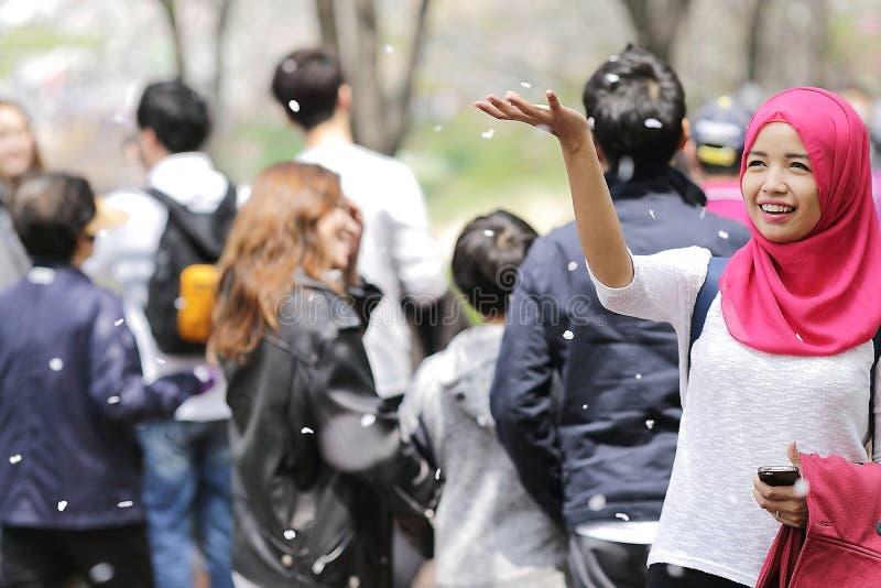 Woman Wearing Red Hijab Behind Person Wearing Black Jacket stock photos