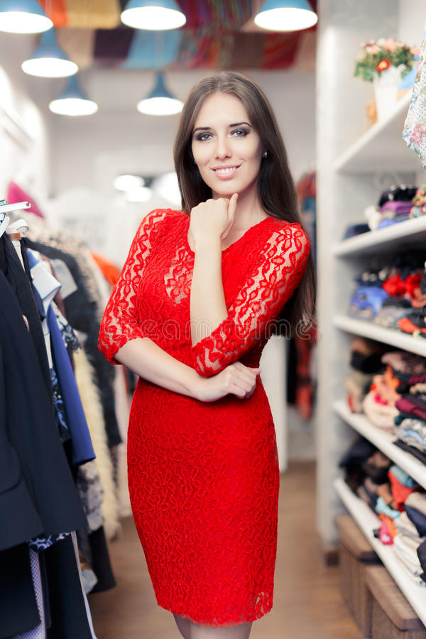 Woman wearing red lace dress in fashion store royalty free stock photo
