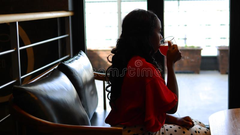 Woman Wearing Red Long-sleeved Blouse Sitting and Drinking Liquid stock images