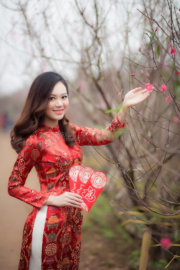 Woman Wearing Red Long-sleeved Dress Holding Pink Petaled Flower stock photo