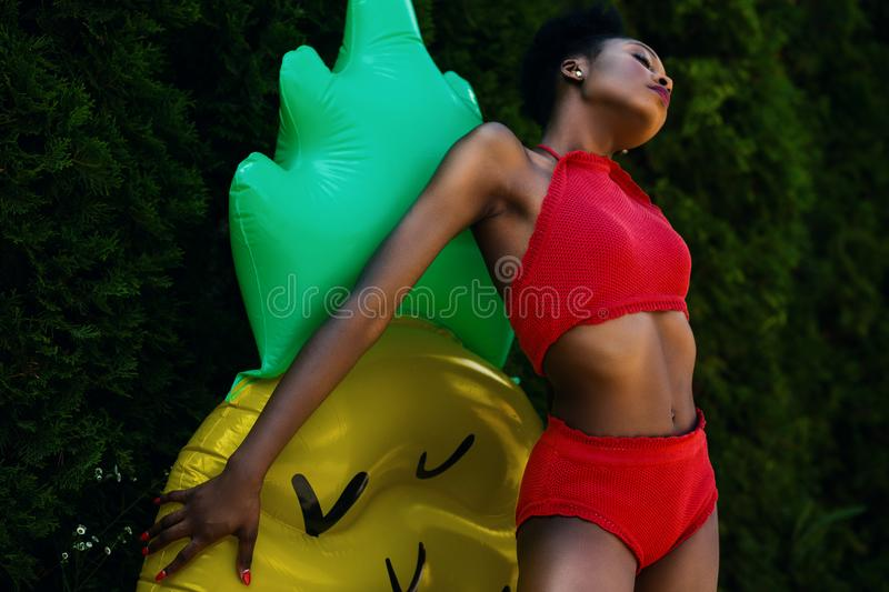 Woman Wearing Red Top and Bottoms Leaning on Yellow and Green Inflatable Standee royalty free stock images
