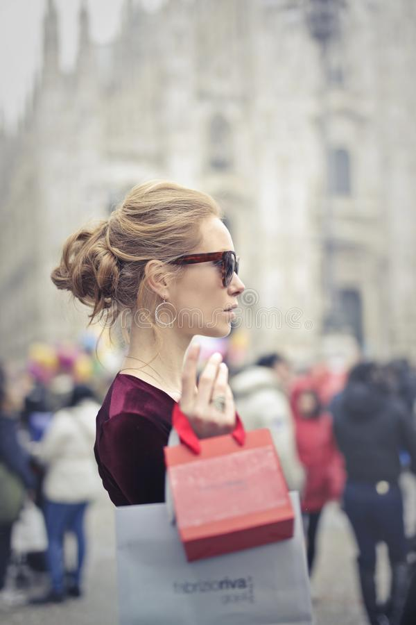 Woman Wearing Red Top Carrying Red Paper Tote Bag stock photo