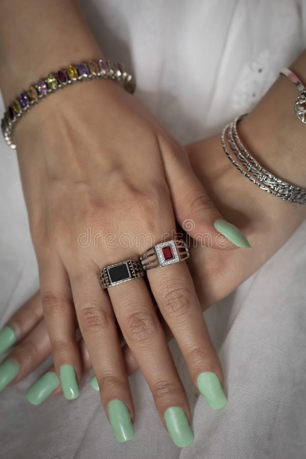 Woman wearing ring and bangle jewellery. Indian woman wearing jewellery like ring and bangles on hand with green color nails. Ethnic and traditional image can royalty free stock images
