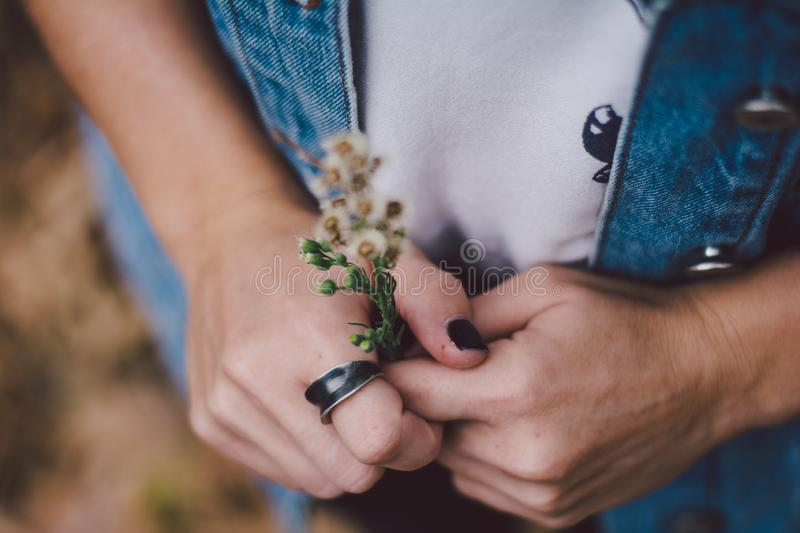 Woman wearing a ring. And holding flowers stock photos