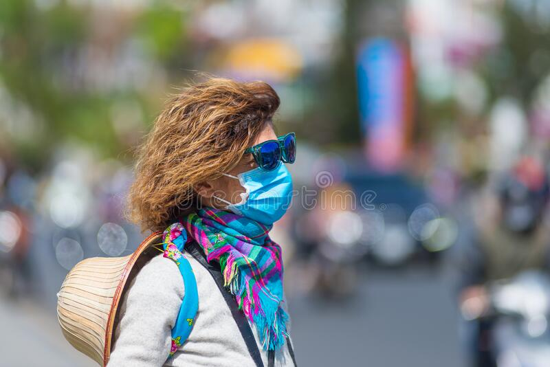 Woman wearing sanitary mask outdoors in Da Lat city centre Vietnam. Medical mask protection against risk of chinese flu virus stock photo