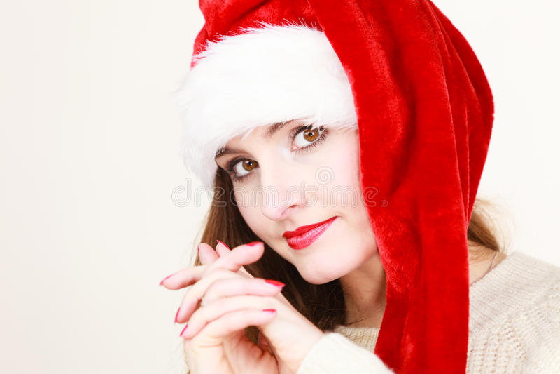 Woman wearing santa claus hat portrait. Christmas time. Young latin pensive woman wearing santa claus hat portrait. Studio shot royalty free stock photo