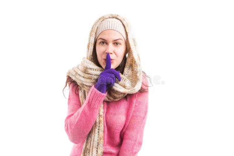Woman wearing scarf and hat showing shush silent gesture royalty free stock photo