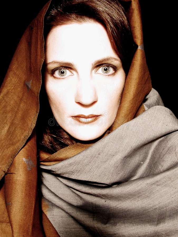 Woman Wearing Scarf Portrait 3. A portrait of a woman wrapped in a scarf. Rich colors and classy presentation stock image