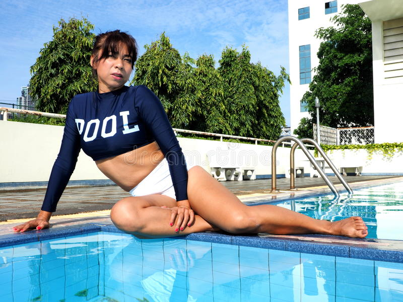 Woman wearing swimsuit sits at the edge of a pool royalty free stock photography