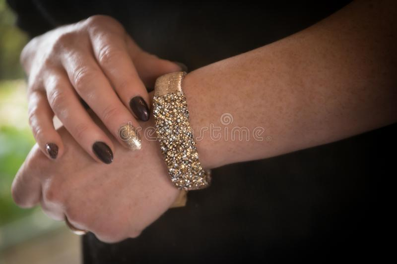 Woman wearing shiny bracelet in gold color and fake diamonds around her arm. Fingers with nail polish. royalty free stock photos