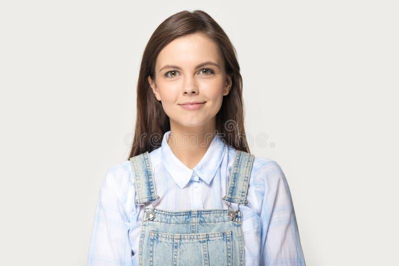 Woman wearing shirt denim coverall posing on grey studio background stock photo