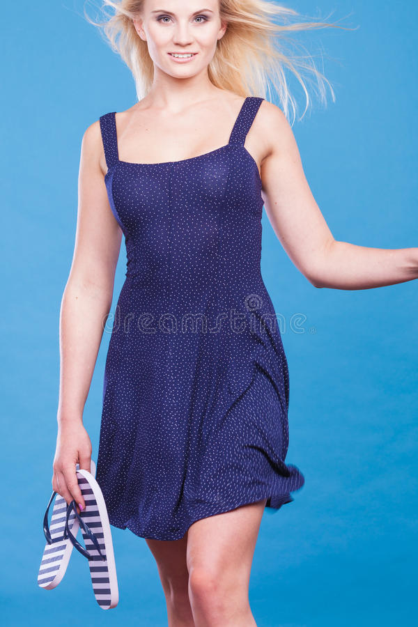 Woman wearing short navy dress holding flip flops. Summer trendy fashionable outfit ideas concept. Woman wearing short navy dress holding flip flops stock photo