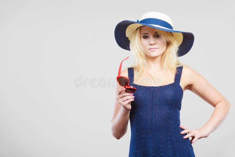 Woman wearing short navy dress and sun hat royalty free stock photo