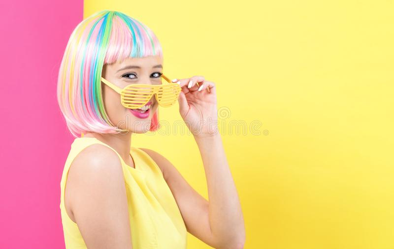 Woman wearing shutter shades sunglasses in a colorful wig stock photography
