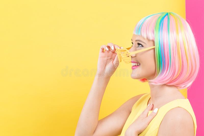 Woman wearing shutter shades sunglasses in a colorful wig royalty free stock photos