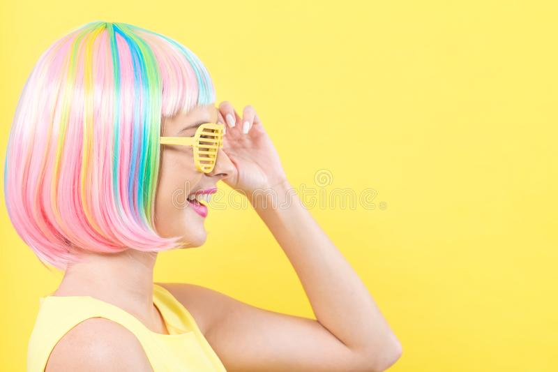 Woman wearing shutter shades sunglasses in a colorful wig royalty free stock photography