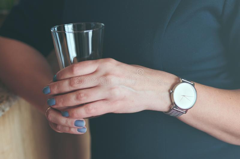 Woman wearing silver wristwatch and blue dress holding glass of stock images