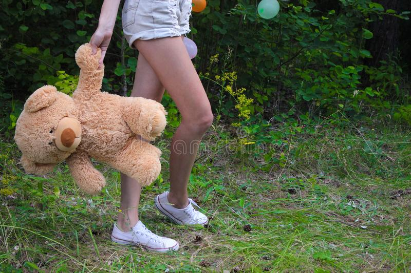 Woman wearing skirt and high heels, holding toy bear near her legs, view of the back lower body part, on white background. Woman wearing skirt and high heels royalty free stock image