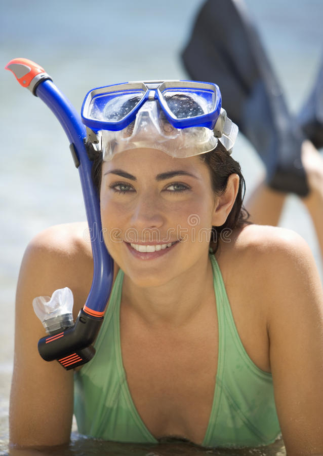A woman wearing snorkeling equipment lying on a beach royalty free stock photo