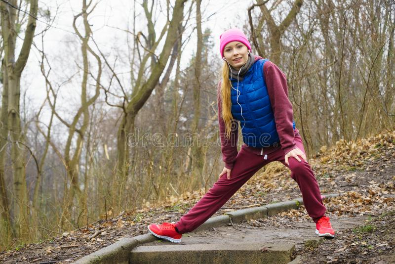 Woman wearing sportswear exercising outside during autumn stock image