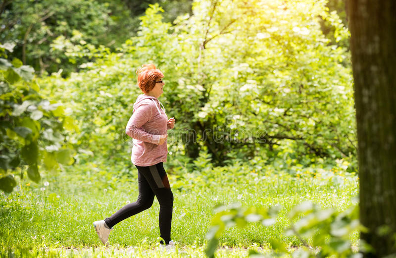 Woman wearing sportswear and running in forest at mountain royalty free stock image