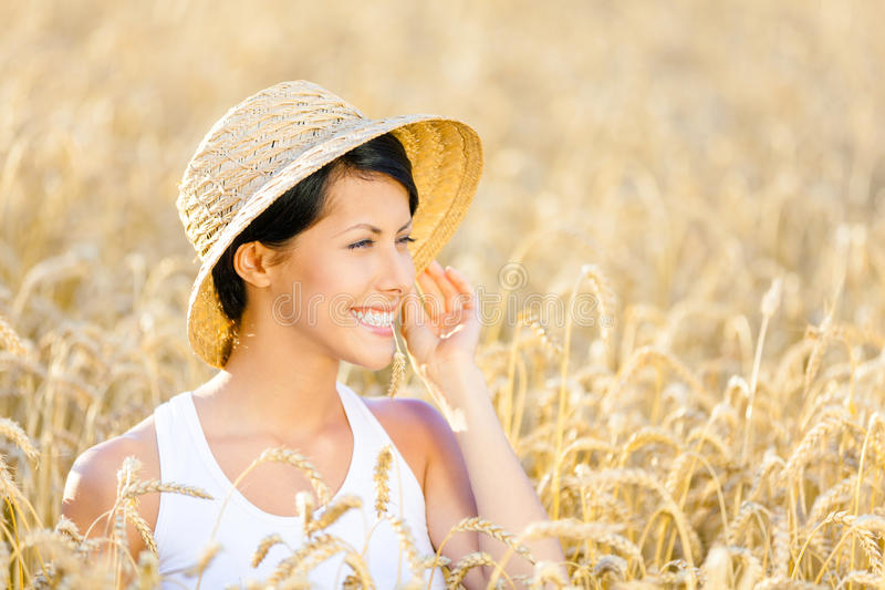 Woman wearing straw hat is in rye field. Concept of rural lifestyle royalty free stock image