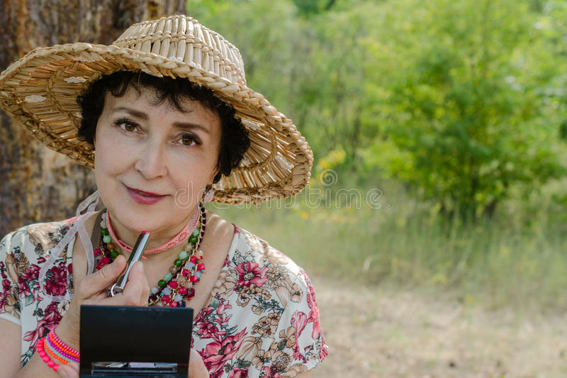 Woman wearing a straw hat, uses her lipstick in nature. Elderly woman wearing a straw hat, uses her lipstick in nature, looking in the mirror royalty free stock images