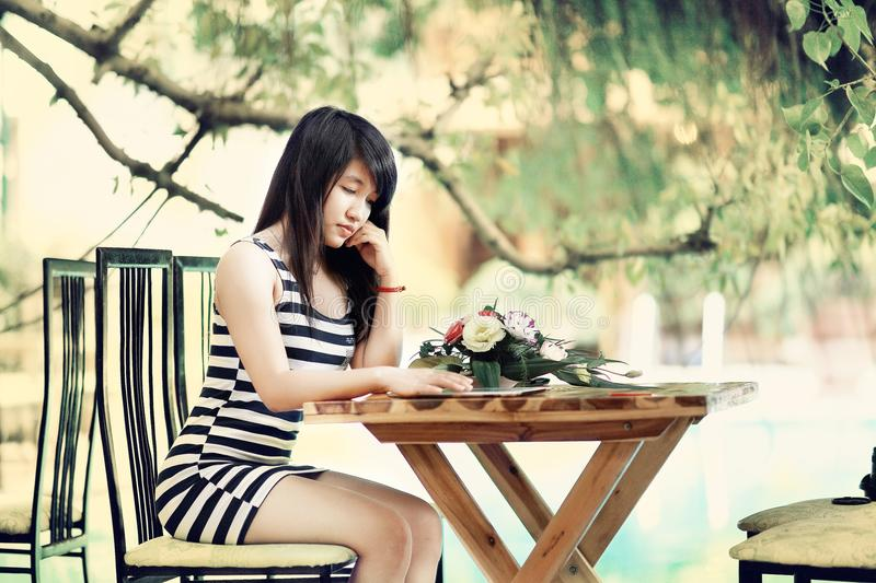 Woman Wearing Stripe Tank Bodycon Dress Sitting on Chair Leaning on Table stock photos