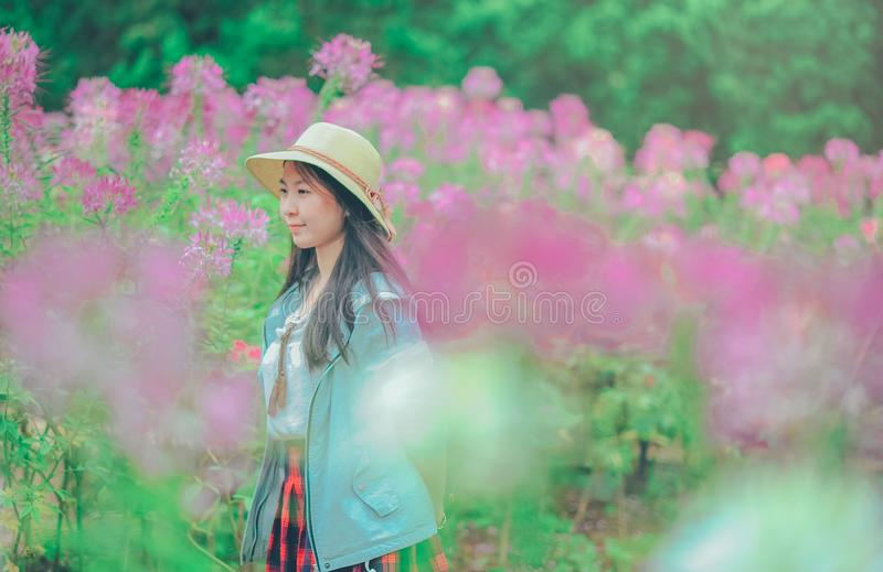 Woman Wearing Sun Hat and Blue Jacket Standing Surrounded by Flowers royalty free stock photos