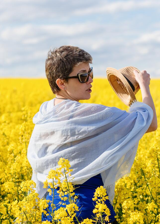 Woman  wearing sunglasses and blue scarf taking off her hat in yellow rapeseed field on warm sunny spring day. Woman  wearing the sunglasses and blue scarf royalty free stock photos