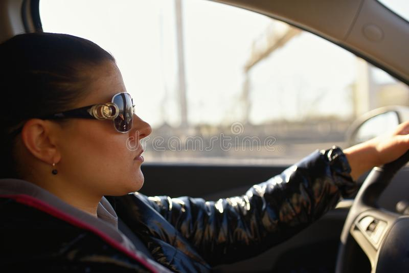 Woman wearing sunglasses drives car and is concentrated looks at road.  stock photography