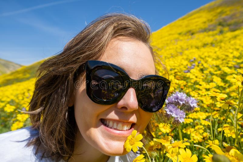 Woman wearing sunglasses sits and poses in a field of yellow wildflowers at Carrizo Plain National Monument for California. Superbloom. Concept for spring royalty free stock photos