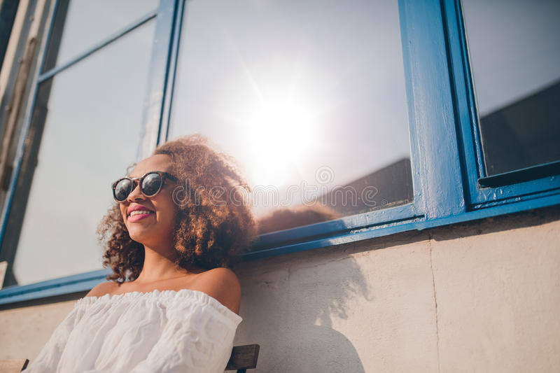 Woman wearing sunglasses sitting outside her house. Outdoor shot of happy young african female sitting outdoors and smiling. Woman wearing sunglasses sitting royalty free stock images