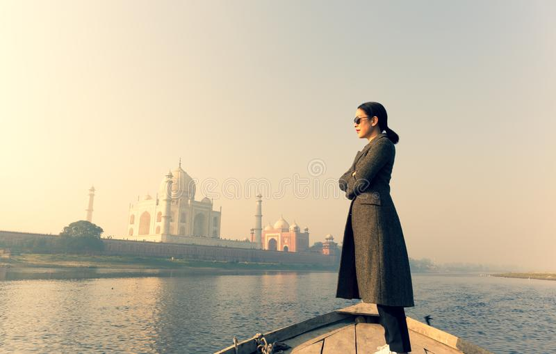 Woman with wearing sunglasses standing on a boat with Taj Mahal in background. royalty free stock photo